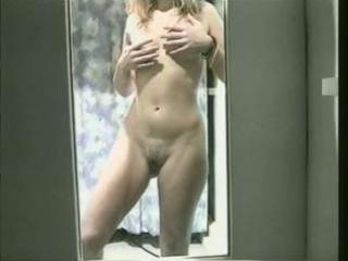 blonde young poses into front of the mirror in